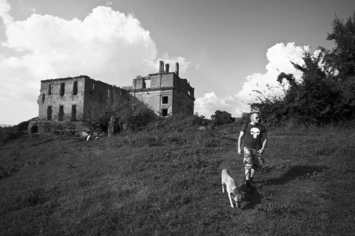 dog man church abandoned ruins field clouds black and white antica monterano rome italy